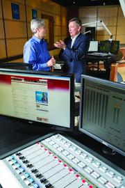 IMG College CEO Ben Sutton Jr., right, talks with Chris Ferris, vice president of broadcasting.
