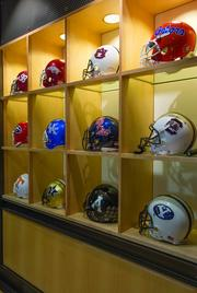 A collection of football helmets is displayed at IMG's office in Winston-Salem. The helmets are from college teams represented by IMG.