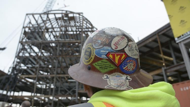 An Iron workers watches the topping out ceremony on the Old Parkland campus.