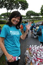 Sharon Brown, president of First Hawaiian Bank Foundation, volunteering to help pass out water to the military's Sounds of Freedom runners at the Kaiser Permanente Great Aloha Run.