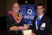 "Gene Davis, left, public relations manager at Ronald McDonald House Charities of Hawaii receives a donation  of $700 raised through DECA's ""Miracle Minute"" fundraiser from DECA Hawaii president Justin Scharf at the Career Technical Student Organization awards banquet."