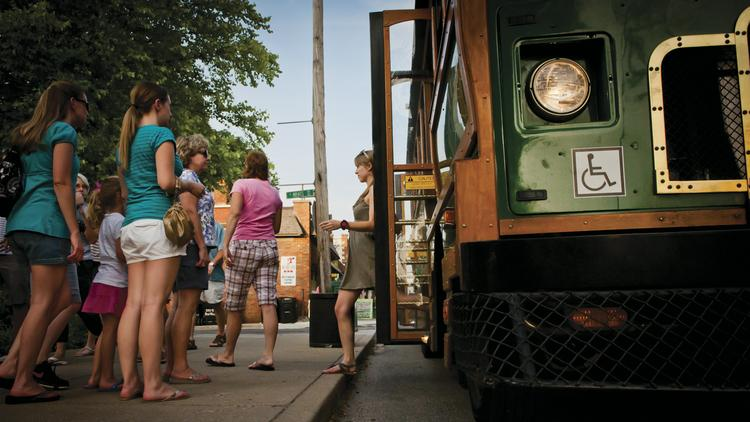 Passengers exit a trolley on Frankfort Avenue.