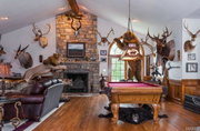 """19217 Brookhollow Drive: The home features several fireplaces, including a stone one in this """"hunt room."""""""
