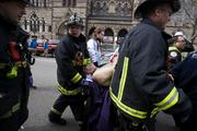 Firemen carry an injured person where two explosions occurred along the final stretch of the Boston Marathon on Boylston Street in Boston, Massachusetts, U.S., on Monday, April 15, 2013. Two powerful explosions rocked the finish line area of the Boston Marathon near Copley Square and police said many people were injured. Photographer: Kelvin Ma/Bloomberg