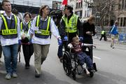 First responders tend to a young boy in a wheelchair, where two explosions occurred along the final stretch of the Boston Marathon on Boylston Street in Boston.