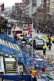 First responders rush to where two explosions occurred along the final stretch of the Boston Marathon on Boylston Street in Boston on Monday