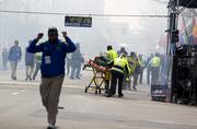 First responders rush to where two explosions occurred along the final stretch of the Boston Marathon on Boylston Street in Boston on Monday.