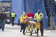 First responders transport the wounded where two explosions occurred along the final stretch of the Boston Marathon on Boylston Street in Boston, Massachusetts, U.S., on Monday, April 15, 2013. Two powerful explosions rocked the finish line area of the Boston Marathon near Copley Square and police said many people were injured. Photographer: Kelvin Ma/Bloomberg