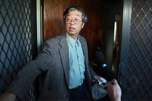 Dorian S. Nakamoto, identified by Newsweek magazine as the founder of Bitcoin, stands surrounded by members of the media as he arrives home in Temple City, California, on March 6, 2014.