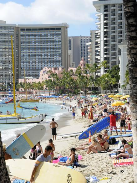 Tourists crowd Waikiki Beach fronting hotels from the Sheraton Waikiki and The Royal Hawaiian to the Moana Surfrider hotels in this March 2013 file photo. Hawaii hotels earned a record $5.3 billion in total revenue in 2013, according to a report by Hospitality Advisors LLC and Smith Travel Research.