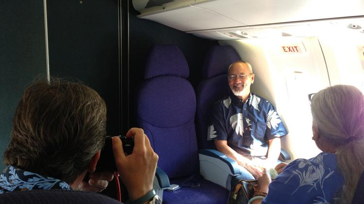 Hawaiian Airlines President and CEO Mark Dunkerley, left, snaps a photo of designer Siz Zane, who designed the aircraft livery for the airline's new Ohana by Hawaiian turboprop subsidiary, aboard the new airline's inaugural flight to Molokai on Tuesday.