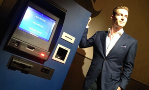 CEO of Robocoin stands beside one of his company's Bitcoin ATMs in Austin, Texas.