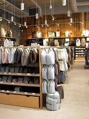 A shot of clothing and travel accessories like suitcases and neck pillows at Muji's San Jose store.