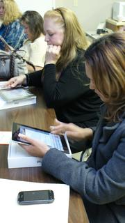 Realty World Alliance agents Sheri Proctor, left, and Lucy Ferrer Gonzalez, foreground, learn functions of their new iPads today. Broker/owner Greg Fox taught the class at the company's West 13th Street office after distributing the devices.