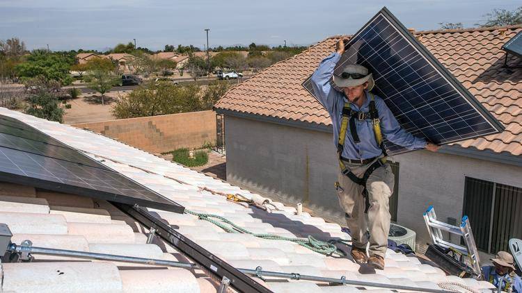 Eliel Ortega, an installer with Sun Valley Solar Solutions, carries a panel on a rooftop in Gilbert. APS predicts that along with the doubling of renewable energy, rooftop solar power generation is expected to triple by 2029.