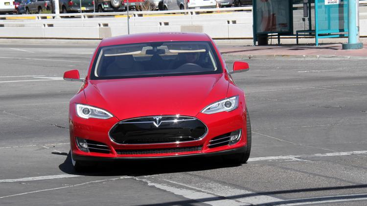 "Dr. Barbara McAneny's ""arrest-me-red"" Model S on Central Avenue is silent as it drives by. ""The first time I went under the underpass, I heard all these noises from other cars I'd never heard before,"" she says. Photos by Randy Siner 
