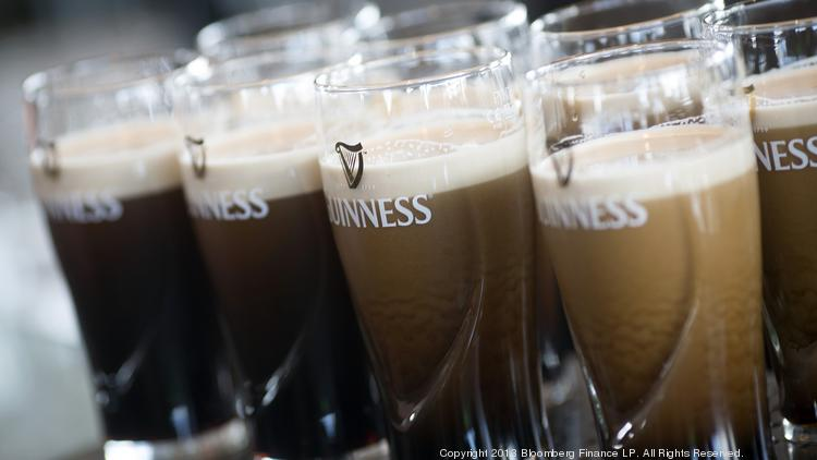 Freshly poured Guinness settles in branded pint glasses on the bar in the Guinness Gravity Bar at the St. James's Gate Brewery, in Dublin, Ireland.