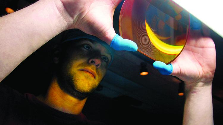 A zinc selenide lens that will be used in a military thermal imaging system is prepared at II-VI Inc.'s manufacturing plant in Saxonburg in a 2010 file photo.