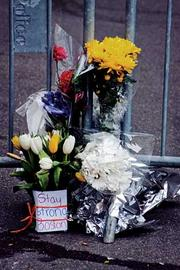 "A lone flower arrangement at the corner Clarendon and Newbury tells residents ""Stay Strong Boston."""