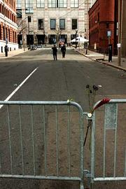 A few simple flowers grace the barriers on Gloucester Street the day after the Boston Marathon bombings.