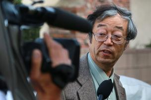 Dorian Satoshi Nakamoto, identified by Newsweek magazine as the inventor of Bitcoin, speaks to members of the media as he arrives home in Temple City, California, on Thursday, March 6, 2014. Nakamoto, 64, denied involvement in the digital currency before leading reporters on a multi-vehicle car chase and entering an Associated Press bureau.