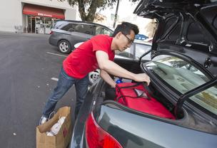 Tony Xu of DoorDash loads up the meals from Siam Royal.
