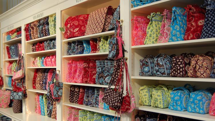 Vera Bradley Bags And Other Products Sit On Shelves.
