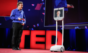 Chris Anderson, TED chief, speaks to a robot displaying video of Edward Snowden at the TED Conference in Vancouver, Canada, on March 18, 2014.