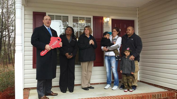 Wells Fargo (NYSE:WFC) Regional President Kendall Alley presents U.S. Army Sgt. Brandon Hunt and his family with a ceremonial key to a mortgage-free home provided by the San Francisco-based bank and Operation Homefront.
