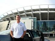 Cincinnati Bengals punter Kevin Huber stands beside an uberX car.