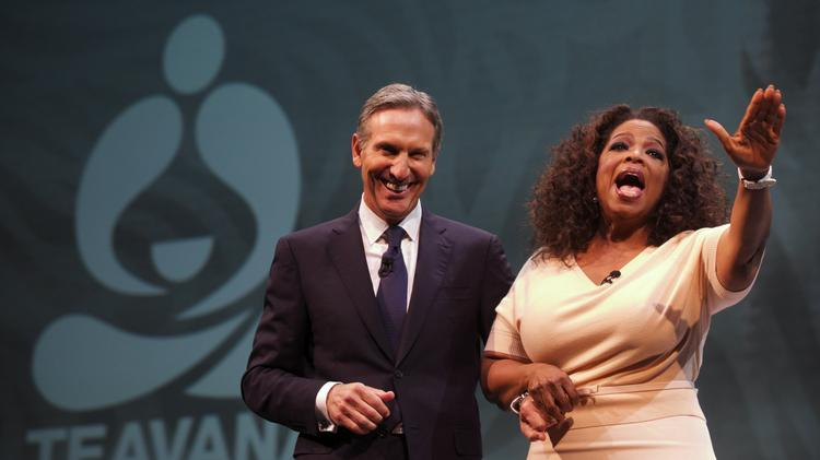Starbucks CEO, President and Chairman Howard Schultz, left, introduces Oprah Winfrey to talk about Oprah Chai Tea during the Starbucks annual meeting Wednesday at Seattle's McCaw Hall.