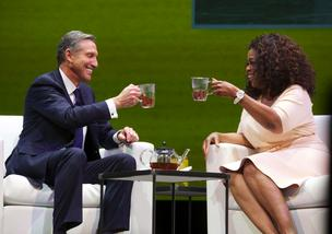 (BUSINESS JOURNAL PHOTO | Stephen Brashear) Starbucks CEO, President and Chairman Howard Schultz, left, and Oprah Winfrey toast Oprach Chai Tea during the Starbucks Annual Shareholders Meeting at McCaw Hall in Seattle Wednesday March 19, 2014.