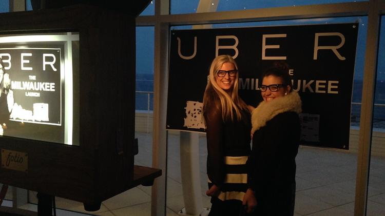 Two attendees pose in costume for a photobooth shot during Uber's Milwaukee debut event.