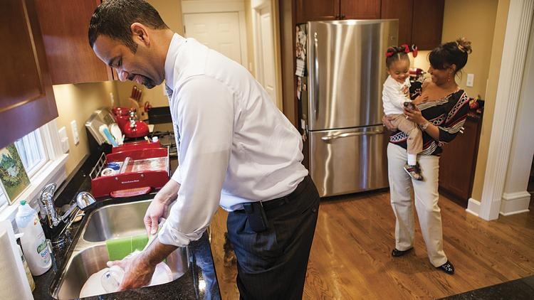 Frost Brown Todd LLC attorney Jason Williams, left, washes the dishes at home. His wife, District Court Judge Erica Lee Williams, and daughter Jacqueline Chase Williams, 2, are shown in the background.