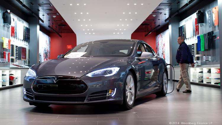 A Tesla Motors Inc. Model S connected to a charger sits on display at the company's store in Short Hills, N.J. N.J. Gov. Chris Christie's administration blocked Tesla, the electric-car maker that doesn't have franchised retail dealers, from direct auto sales in a move the company said could shutter its only two stores in that state. Photographer: Emile Wamsteker/Bloomberg