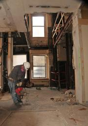 A worker drills through the floor to create space for a new staircase in the Pioneer Building.