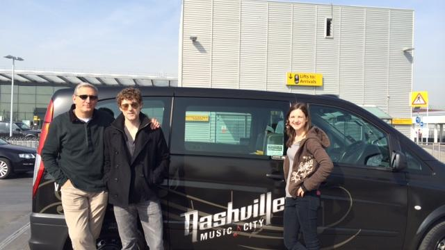 """Butch Spyridon and the Nashville-based band Striking Matches stand with London's """"Music City"""" taxi."""