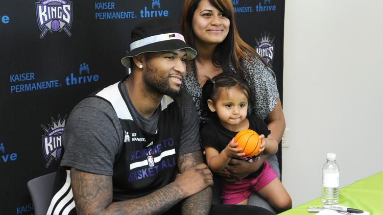Sacramento Kings center DeMarcus Cousins was on hand at Kaiser Permanente's ShopKP retail front at Florin Towne Centre in Sacramento. He was signing autographs. Here, Jessie Bursiaga and Genesis Espinoza pose for a photo with Cousins.
