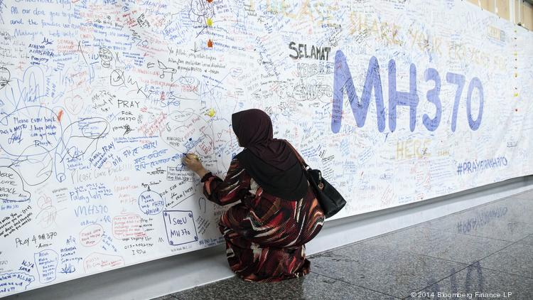 A woman writes a message on a banner for missing Malaysian Airline Flight 370 at Kuala Lumpur International Airport (KLIA) in Sepang, Malaysia.