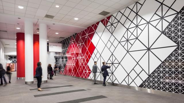"""Sandra Fettingis created """"I Know You Know That I Know,"""" a 160-foot-long painting that spans an entire hallway in the Colorado Convention Center. It aims to create an environment that envelops the viewer in a repetitive pattern-filled corridor."""