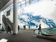 """A 95-by-95 foot mural by Mindy Bray, """"The Heavy is the Root of the Light,"""" covers an entire wall behind a two-story escalator at the Colorado Convention Center. The painting is based on photographs of the Platte River at nearby Confluence Park, the site where gold was first discovered leading to the founding of Denver in 1858."""