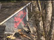 A landslide of mud, trees and rocks near the town of Oso east of Arlington wrecked houses and killed at least 14 people. The red X indicates rescue crews have searched this house.