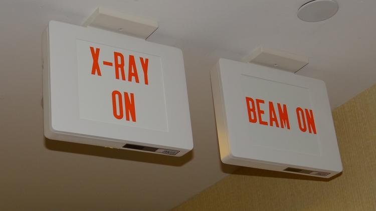 Signs in the radiation oncology department of the Cone Health Cancer Center. The cancer center has six physicists on staff to help provide radiation treatment and plans to replace one of its four linear accelerators.