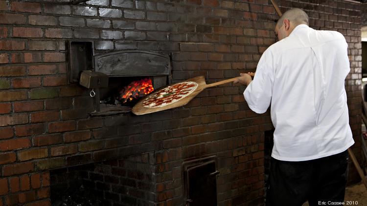 A Grimaldi's Pizzeria employee bakes a pizza. The restaurant opened its first Colorado location March 24.