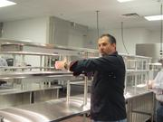 Executive Chef Johnnie Dooher demonstrates how the massive kitchen operates.