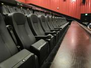 Leather seats are equipped with counters in front for food and drinks. Menus and pencils are stored underneath for ordering during the movie.
