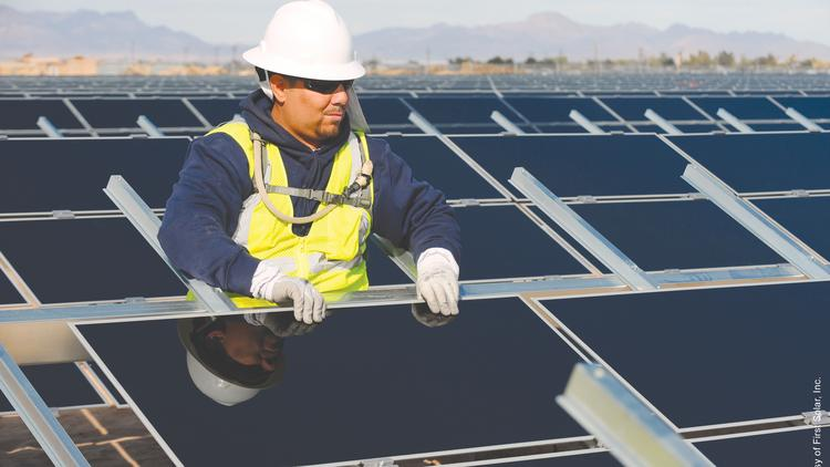 A worker with First Solar Inc. installs a panel during one of the company's recent utility project installations. The District is making a play for a massive solar installation on 49 of its buildings.