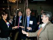 """Ali Winslow of NFP, Paul Lawrance of Benchmark Senior Living, and Kris Aimone of Southcoast Hospitals Group were a few of the over two hundred attendees of the Boston Business Journal's Healthiest Employers 2014 awards breakfast doing a """"mindfulness exercise"""" using a peacock feather."""