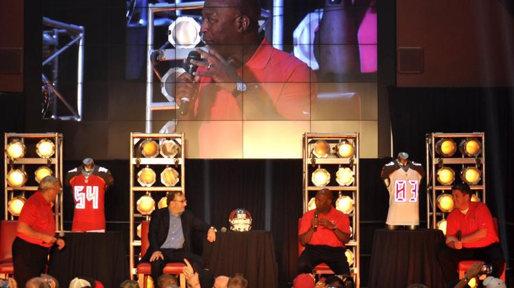 Tampa Bay Buccaneers Head Coach Lovie Smith talks with the crowd of corporate sponsors and season pass members at a new uniform showcase with Buccaneers co-chairman Ed Glazer and General Manager Jason Licht. At left, Gene Deckerhoff hosted the panel discussion.