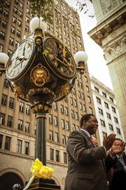 Jacksonville Mayor Alvin Brown applauds the chiming of the restored Jacobs Jewelers clock during the start of One Spark Festival.